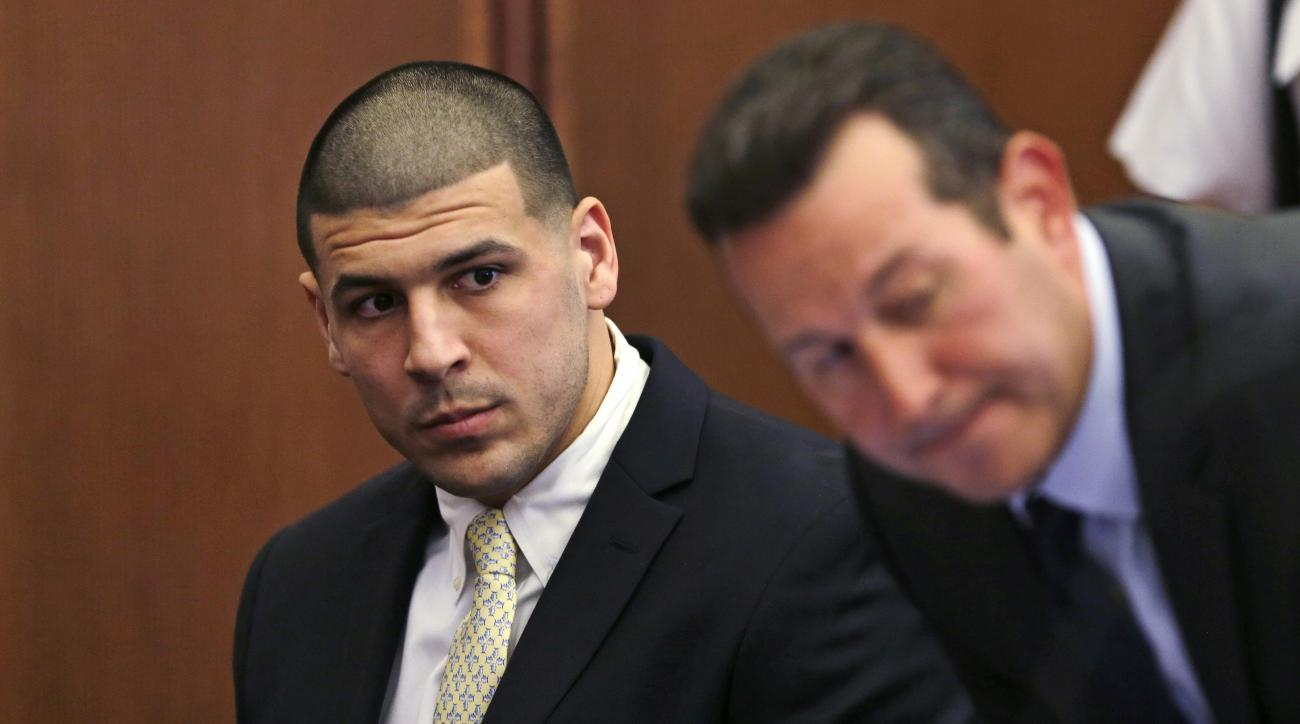 FILE - In this Thursday, July 21, 2016 file photo, Former New England Patriots wide receiver Aaron Hernandez, left, looks down the table at his legal team as his new defense attorney Jose Baez, right, takes a seat during a court appearance at Plymouth Sup