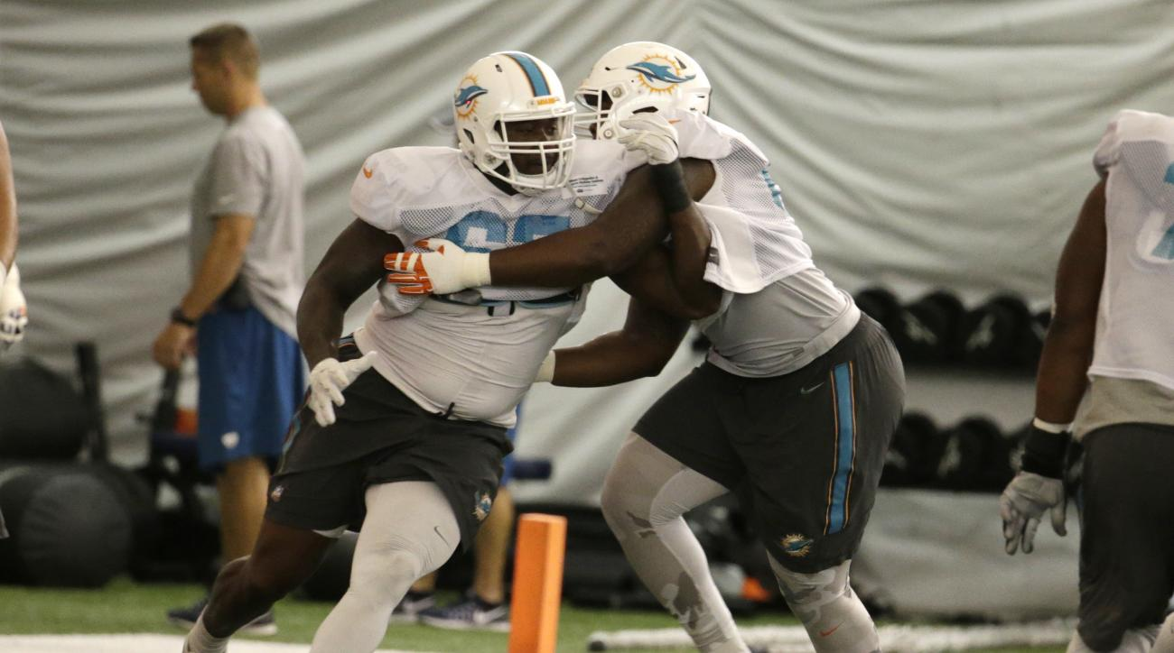 Miami Dolphins offensive lineman Laremy Tunsil (67) does drills with offensive lineman Ruben Carter, right, Wednesday, Aug. 17, 2016, during practice at NFL football training camp in Davie, Fla. (AP Photo/Lynne Sladky)