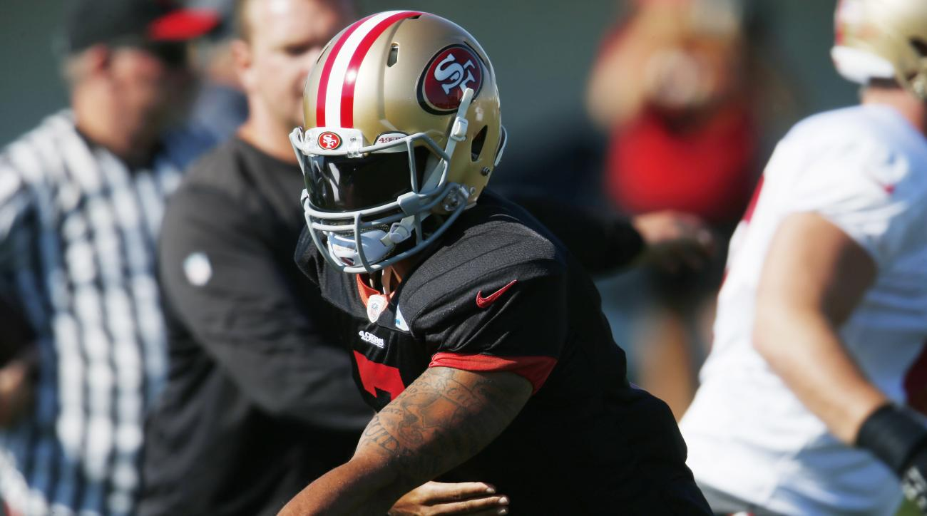 San Francisco 49ers quarterback Colin Kaepernick hands off the ball as players take part in drills before facing the Denver Broncos during the teams' joint NFL football training camp session Thursday, Aug. 18, 2016 in Englewood, Colo. (AP Photo/David Zalu