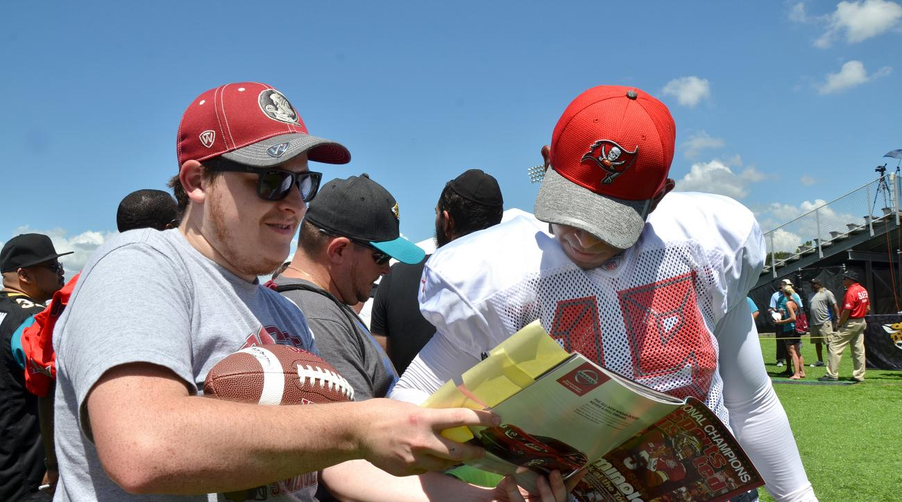 Florida State University fan Rob Coleman, left, gets an autograph from Tampa Bay Buccaneers kicker Roberto Aguayo (19) after at a joint NFL football camp with the Jacksonville Jaguars, Thursday, Aug. 18, 2016, in Jacksonville, Fla.  Aguayo is one of five