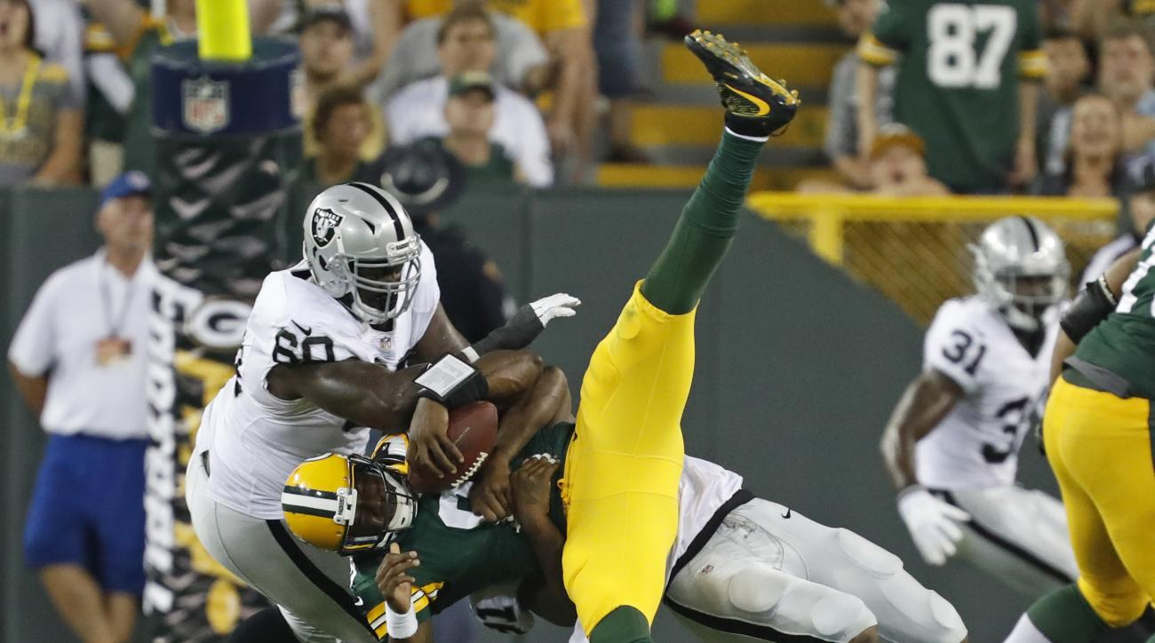 Oakland Raiders defensive tackle Derrick Lott (60) and linebacker Shilique Calhoun sack Green Bay Packers quarterback Marquise Williams, center, during the second half of an NFL preseason football game in Green Bay, Wis., Thursday, Aug. 18, 2016. (AP Phot