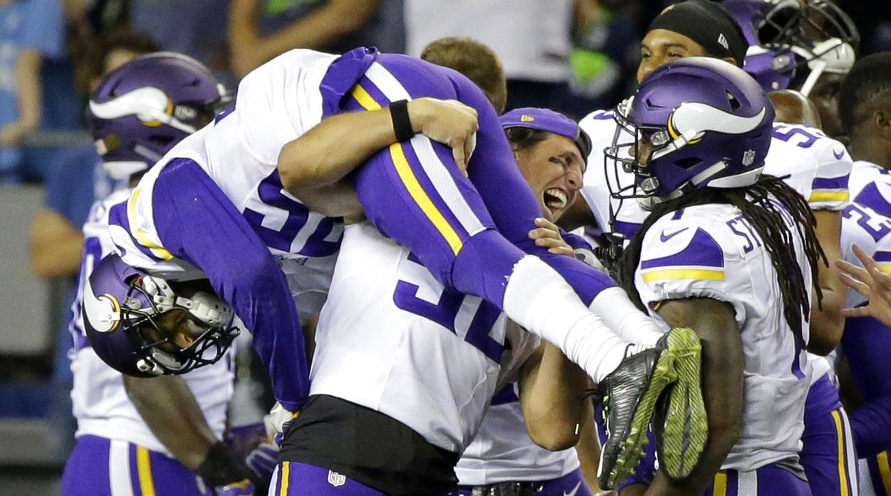 Minnesota Vikings cornerback Marcus Sherels is lifted by outside linebacker Chad Greenway, center, as they celebrate with wide receiver Troy Stoudermire, right, after Sherels intercepted a pass from Seattle Seahawks quarterback Trevone Boykin to score the