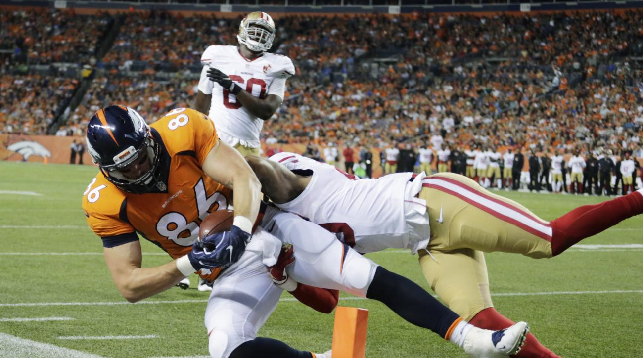 Denver Broncos tight end John Phillips (86) makes a catch for a touchdown as he his tackled by San Francisco 49ers cornerback Kenneth Acker during the second half of a preseason NFL football game, Saturday, Aug. 20, 2016, in Denver. (AP Photo/Jack Dempsey