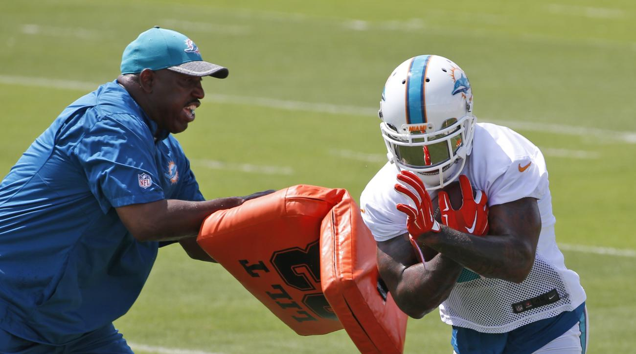 FILE - In this June 14, 2016, file photo, Miami Dolphins running back Isaiah Pead, takes a hit from running backs coach Danny Barrett as he takes part in a drill during the NFL football teams minicamp at the Dolphins training facility in Davie, Fla. Forme