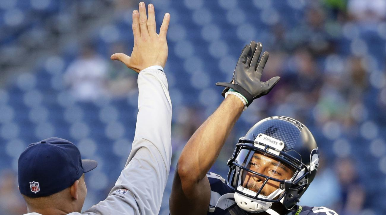 FILE - In this Aug. 18, 2016, file photo, Seattle Seahawks wide receiver Doug Baldwin, right, high-fives tight end Jimmy Graham before the team's preseason NFL football game against the Minnesota Vikings, in Seattle. Last season was a career year for Bald