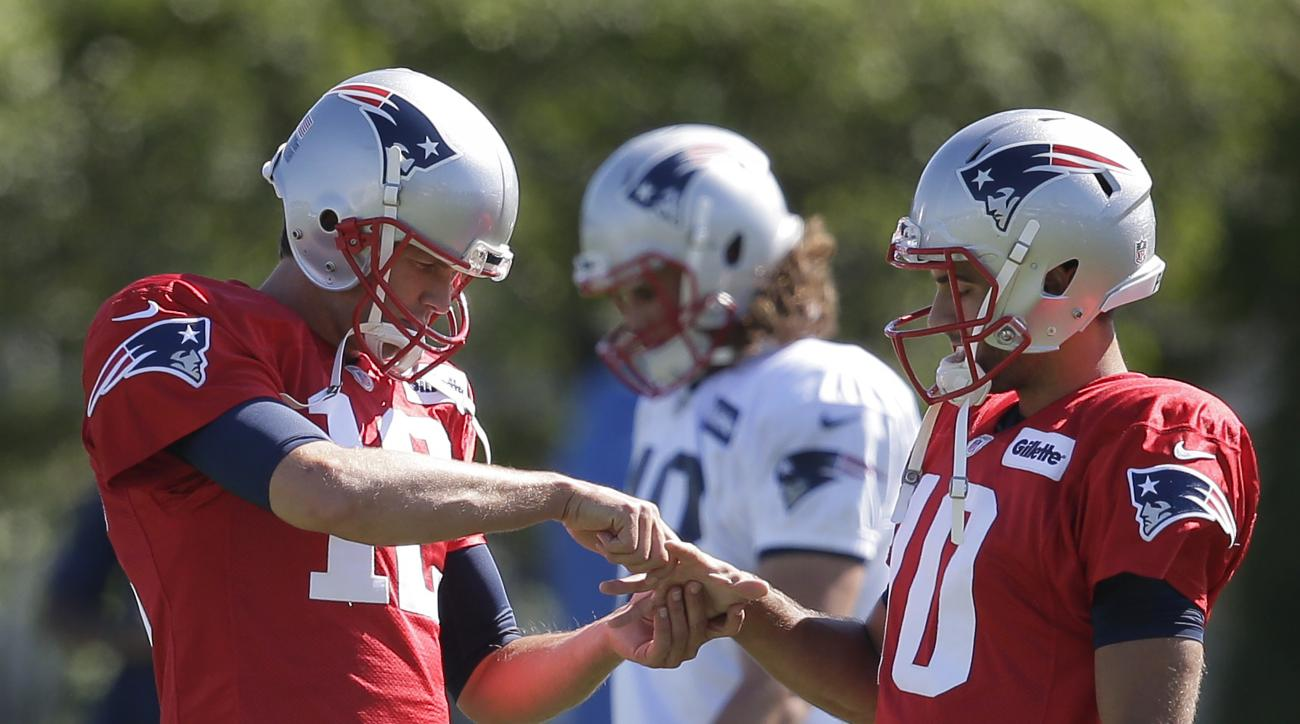 New England Patriots quarterback Tom Brady, left, grasps the hand of quarterback Jimmy Garoppolo, right, during NFL football training camp, Tuesday, Aug. 23, 2016, in Foxborough, Mass. (AP Photo/Steven Senne)