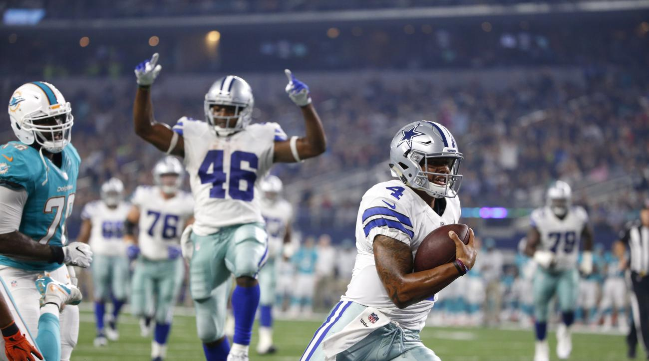 FILE - In this Aug. 19, 2016, file photo, Dallas Cowboys' Dak Prescott (4) runs the ball into the end zone for a touchdown as teammate Alfred Morris (46) celebrates in the first half of an NFL preseason football game agains the Miami Dolphins, in Arlingto