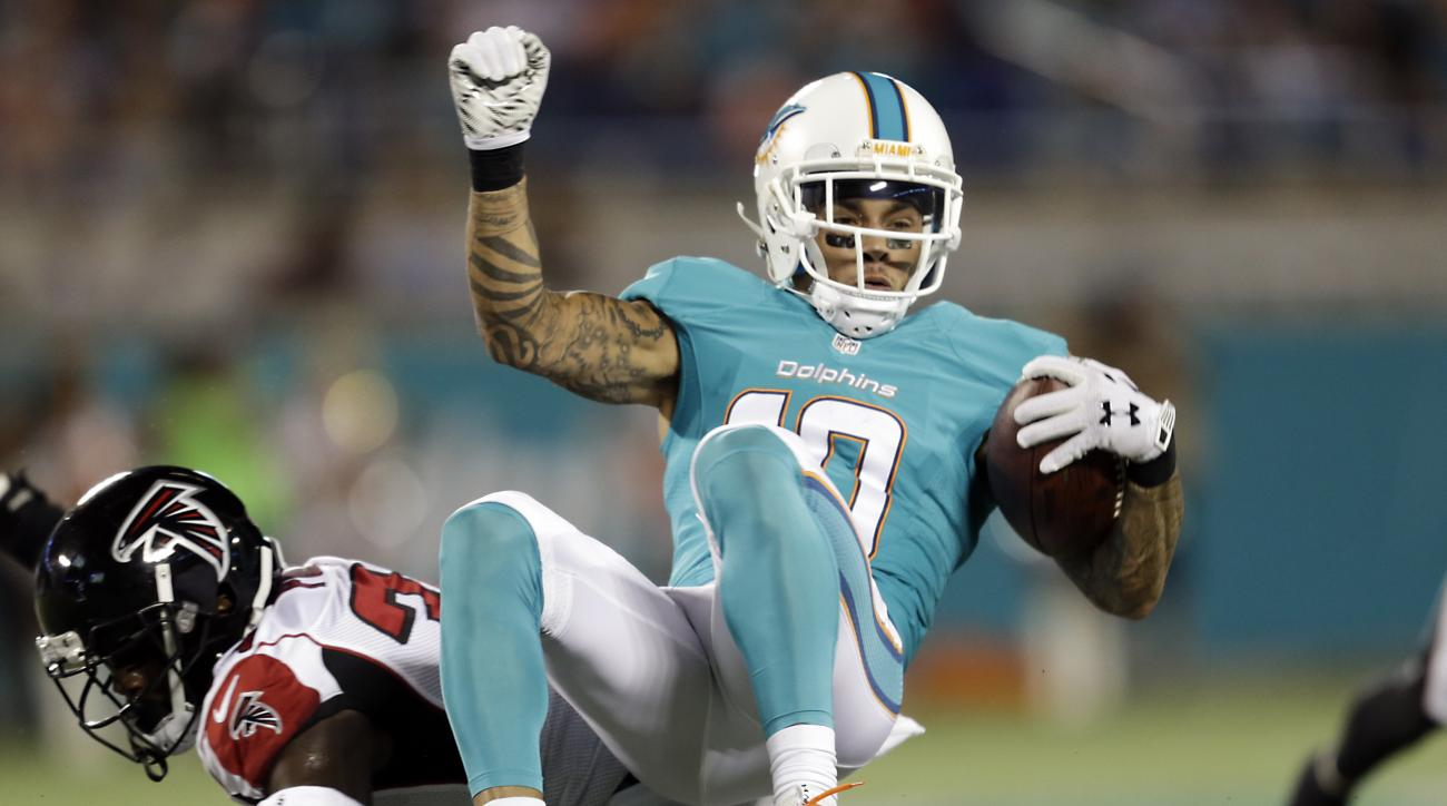 Miami Dolphins wide receiver Kenny Stills, top, is stopped, after a reception, by Atlanta Falcons defensive back Brian Poole during the first half of an NFL preseason football game in Orlando, Fla., Thursday, Aug. 25, 2016.(AP Photo/Willie J. Allen Jr.)