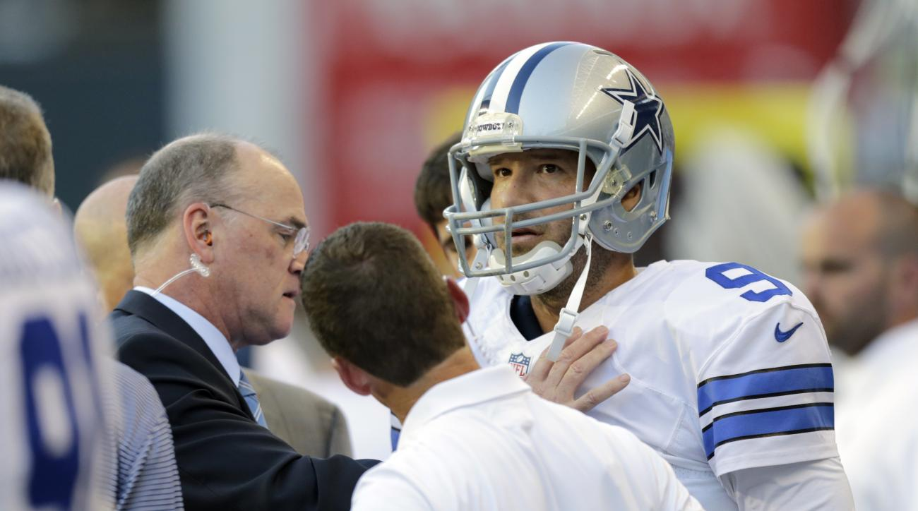 Dallas Cowboys quarterback Tony Romo is examined on the sideline after he left the game with an injury during the first half of a preseason NFL football game against the Seattle Seahawks, Thursday, Aug. 25, 2016, in Seattle. (AP Photo/Stephen Brashear)