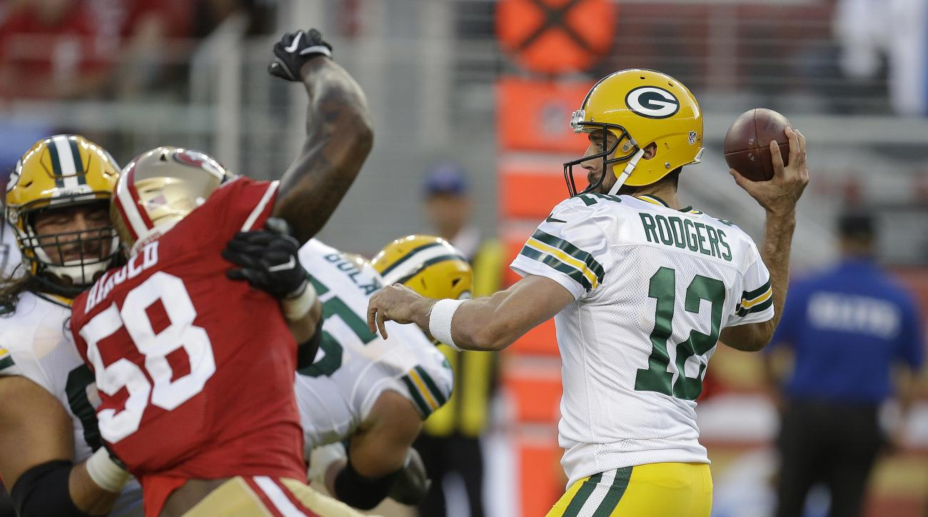 Green Bay Packers quarterback Aaron Rodgers, right, drops back to throw as San Francisco 49ers outside linebacker Eli Harold, left, closes in during the first half of an NFL preseason football game Friday, Aug. 26, 2016, in Santa Clara, Calif. (AP Photo/B
