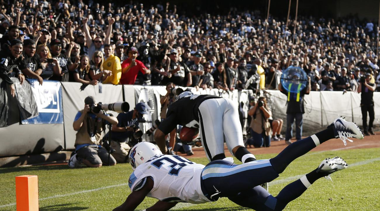 Oakland Raiders wide receiver Amari Cooper, right, scores a touchdown as Tennessee Titans cornerback Jason McCourty, left, looks on during the first half of an NFL preseason football game Saturday, Aug. 27, 2016, in Oakland, Calif. (AP Photo/Tony Avelar)