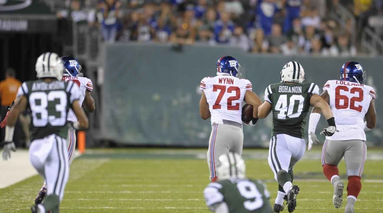 New York Giants defensive end Kerry Wynn (72) returns an interception for a touchdown as New York Jets quarterback Bryce Petty (9) watches during the second half of an NFL preseason football game Saturday, Aug. 27, 2016, in East Rutherford, N.J. (AP Photo