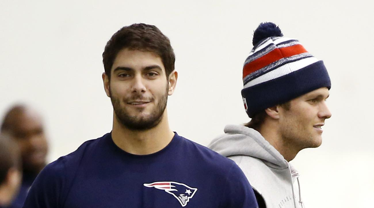 FILE- In this Jan. 23, 2015, file photo, New England Patriots backup quarterback Jimmy Garoppolo, left, holds a football as starting quarterback Tom Brady, right, stands by during a walkthrough at the NFL football team's facility in Foxborough, Mass. Brad