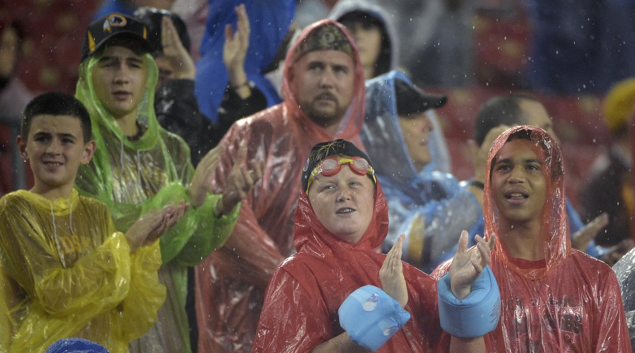 Tampa Bay Buccaneers fans brave heavy rains from tropical storm Hermine as they watch during the second quarter of an NFL preseason football game against the Washington Redskins Wednesday, Aug. 31, 2016, in Tampa, Fla. (AP Photo/Phelan M. Ebenhack)