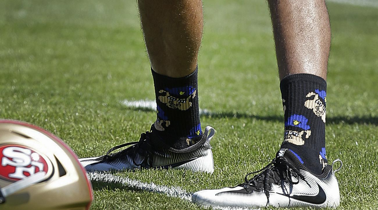 FILE - In this Aug. 10, 2016, file photo, San Francisco 49ers quarterback Colin Kaepernick wears socks depicting police officers as pigs during NFL football training camp at Kezar Stadium in San Francisco. Kaepernick says he has been wearing socks depicti