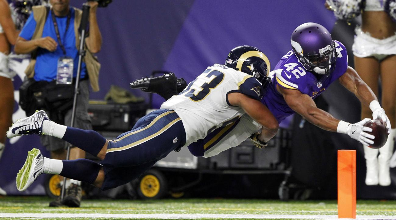 Minnesota Vikings running back Jhurrell Pressley (42) dives into the end zone in front of Los Angeles Rams linebacker Brandon Chubb, left, during a 28-yard touchdown reception in the first half of an NFL preseason football game Thursday, Sept. 1, 2016, in