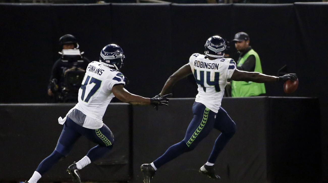 Seattle Seahawks defensive end Ryan Robinson (44) returns an interception for a touchdown against the Oakland Raiders during the second half of a preseason NFL football game Thursday, Sept. 1, 2016, in Oakland, Calif. (AP Photo/Tony Avelar)