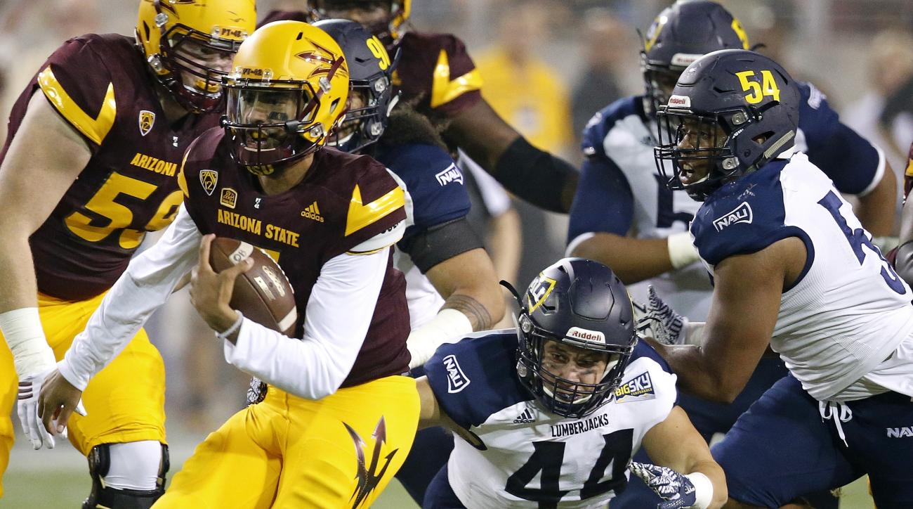 Arizona State's Manny Wilkins, left, runs past Northern Arizona's Jake Thomas (44) and Lorenzo Melvin (54) for a first down during the first half of an NCAA college football game Saturday, Sept. 3, 2016, in Tempe, Ariz. (AP Photo/Ross D. Franklin)