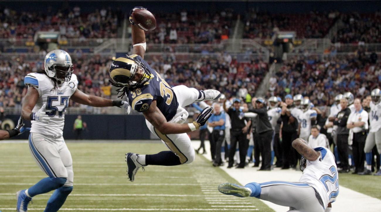 FILE - In this Dec. 13, 2015, file photo, St. Louis Rams running back Todd Gurley, center, scores between Detroit Lions linebacker Josh Bynes, left, and free safety Glover Quin on a 5-yard run during an NFL football game in St. Louis. The Rams offense is
