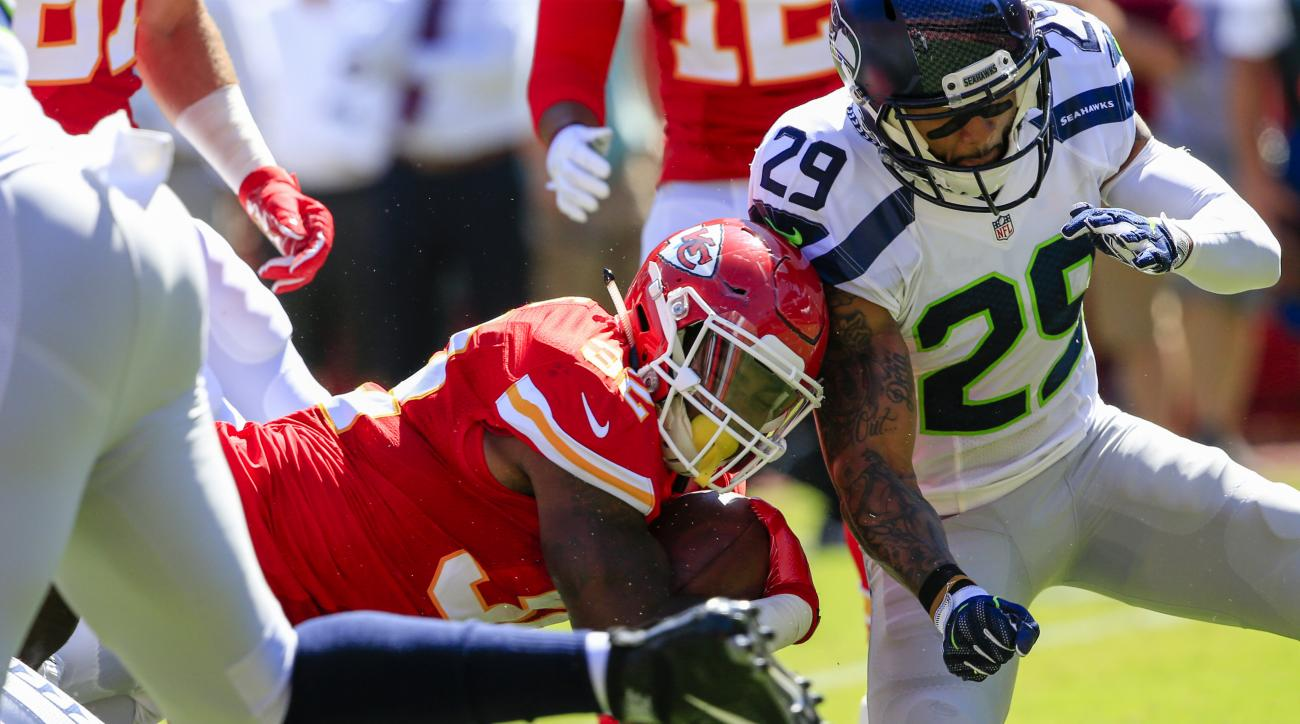 FILE - In this Aug. 13, 2016, file photo, Kansas City Chiefs running back Spencer Ware (32) is tackled by Seattle Seahawks safety Earl Thomas (29) during the first half of an NFL preseason football game in Kansas City, Mo. (AP Photo/Nati Harnik, File)