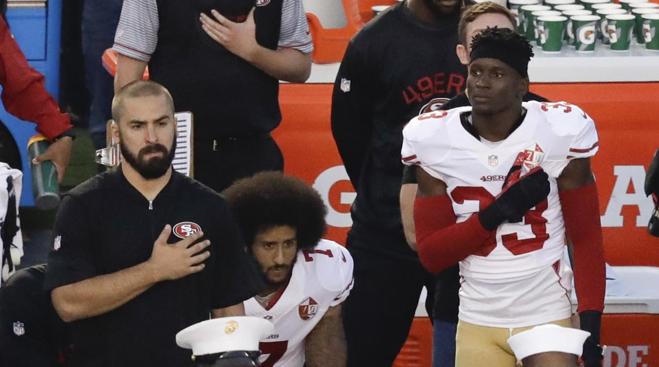 FILE - In this Thursday, Sept. 1, 2016 file photo, San Francisco 49ers quarterback Colin Kaepernick, middle, kneels during the national anthem before the team's NFL preseason football game against the San Diego Chargers, in San Diego. NFL Commissioner Rog