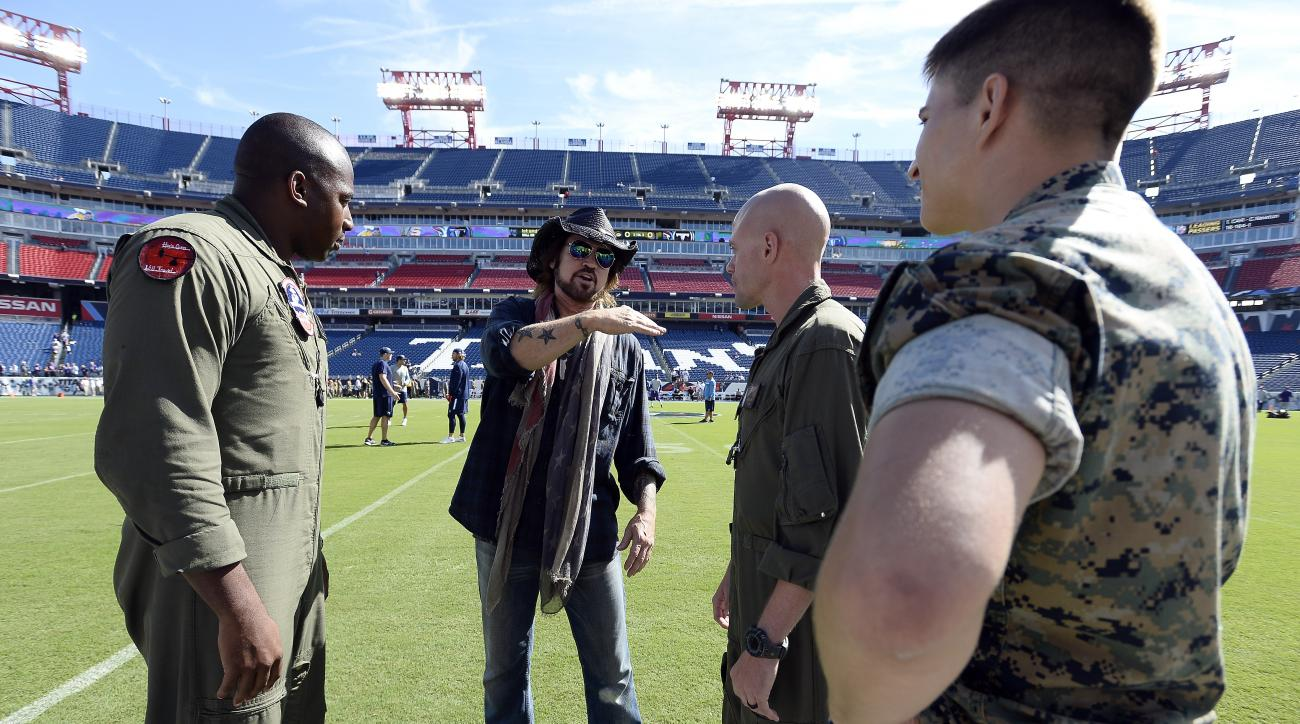 Country music performer Billy Ray Cyrus, second from left, talks with members of the military before an NFL football game between the Tennessee Titans and the Minnesota Vikings Sunday, Sept. 11, 2016, in Nashville, Tenn. Cyrus is scheduled to perform the