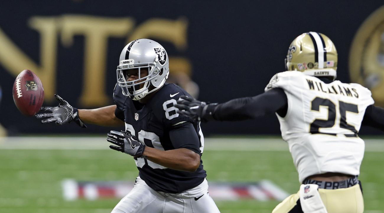 Oakland Raiders tight end Gabe Holmes (82) tries to pull in a pass in front of New Orleans Saints cornerback P.J. Williams (25) in the first half of an NFL football game in New Orleans, Sunday, Sept. 11, 2016. (AP Photo/Bill Feig)