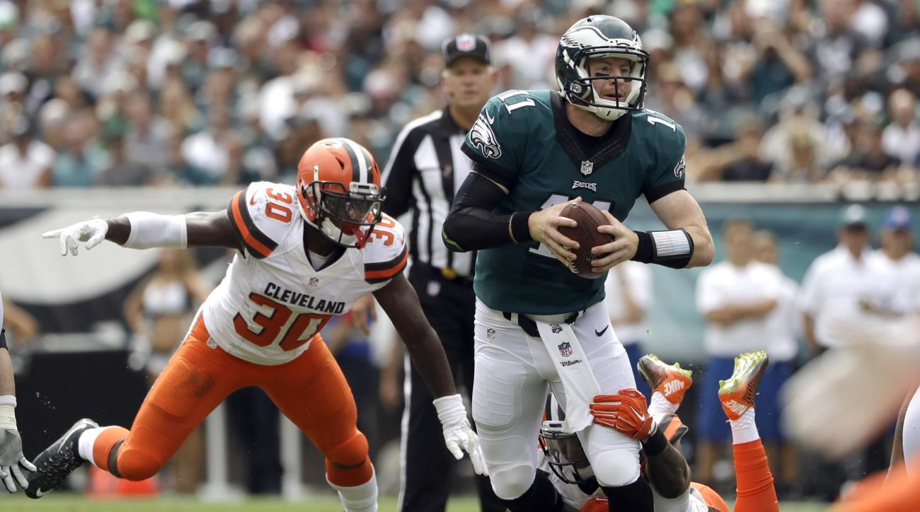 Philadelphia Eagles' Carson Wentz (11) is tackled by Cleveland Browns' Chris Kirksey as Derrick Kindred pursues during the first half of an NFL football game, Sunday, Sept. 11, 2016, in Philadelphia. (AP Photo/Matt Rourke)