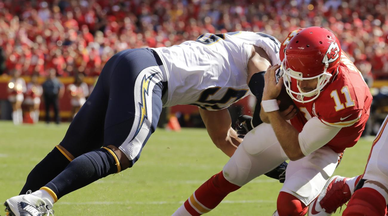 Kansas City Chiefs quarterback Alex Smith (11) carries the ball into the end zone past San Diego Chargers linebacker Tourek Williams (58) to win the game, during overtime in an NFL football game in Kansas City, Mo., Sunday, Sept. 11, 2016. The Kansas City