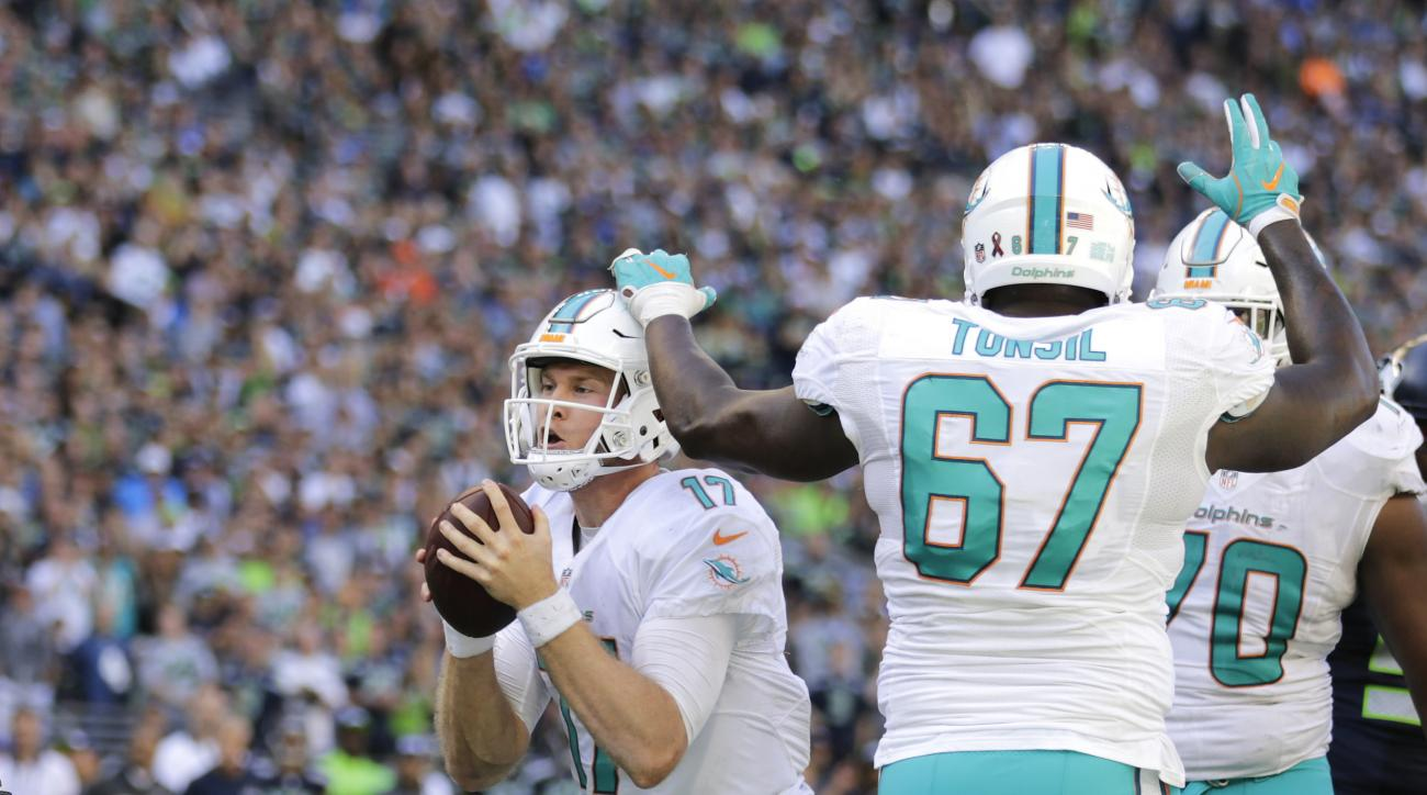 Miami Dolphins quarterback Ryan Tannehill, upper left, scores a touchdown against the Seattle Seahawks in the second half of an NFL football game, Sunday, Sept. 11, 2016, in Seattle. (AP Photo/Stephen Brashear)
