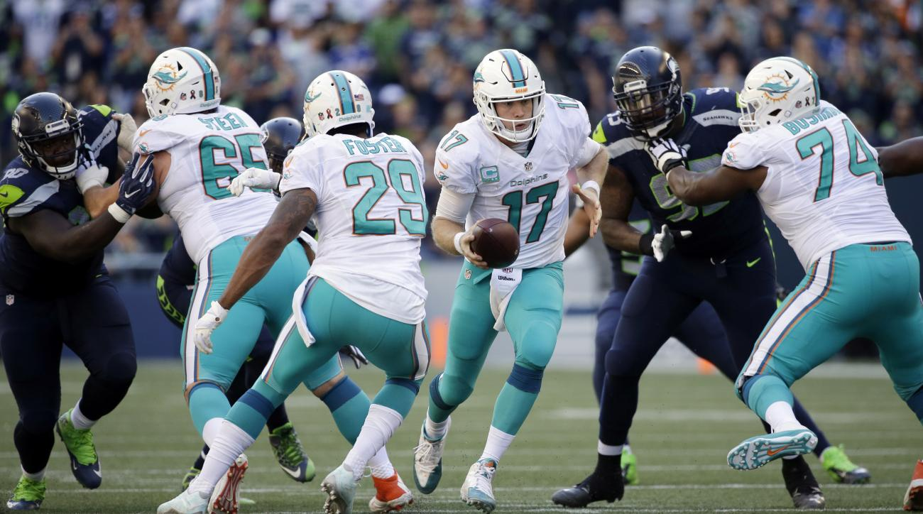 Miami Dolphins quarterback Ryan Tannehill (17) looks to hand off to Arian Foster (29) in the second half of an NFL football game against the Seattle Seahawks, Sunday, Sept. 11, 2016, in Seattle. (AP Photo/Elaine Thompson)