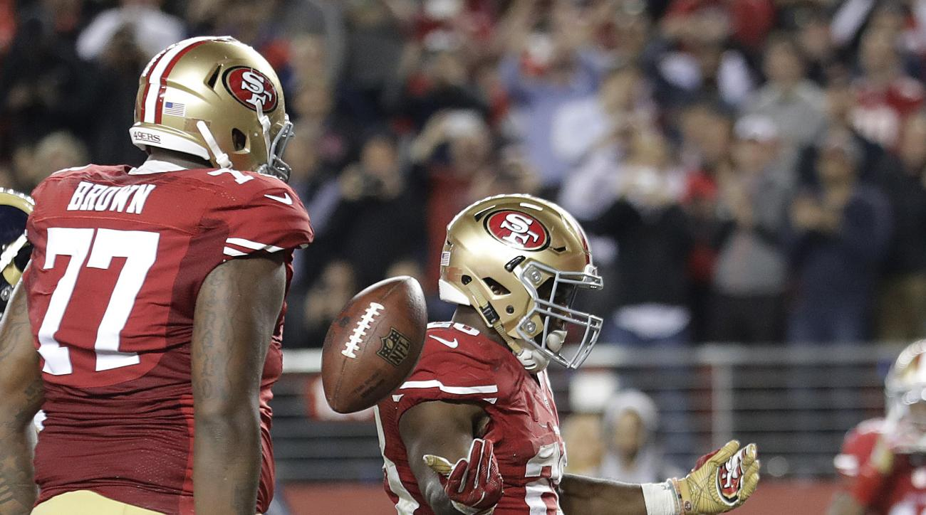San Francisco 49ers running back Carlos Hyde (28) celebrates next to offensive tackle Trent Brown (77) after running for a touchdown against the Los Angeles Rams during the second half of an NFL football game in Santa Clara, Calif., Monday, Sept. 12, 2016