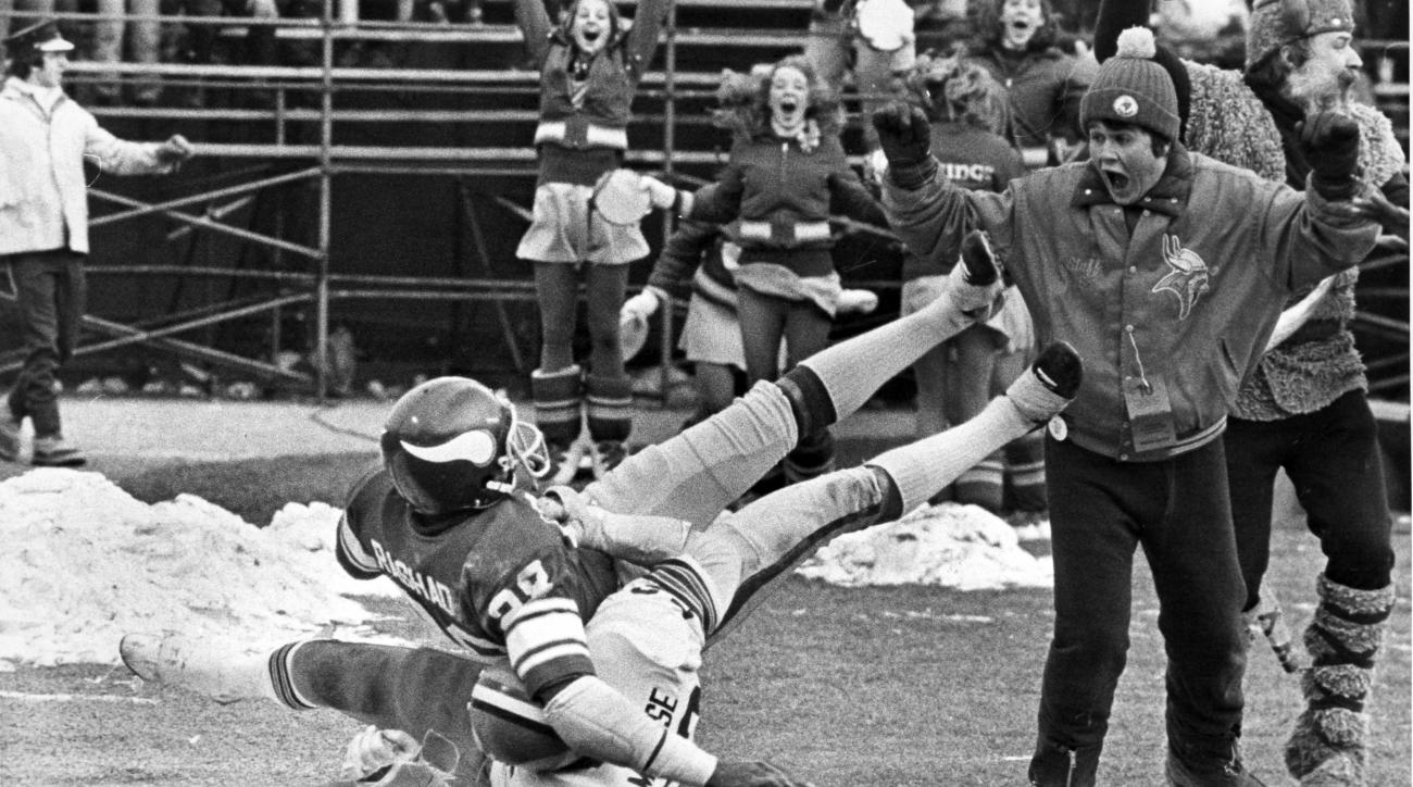 FILE - In this Dec. 14, 1980, file photo, Minnesota Vikings receiver Ahmad Rashad, top, tumbles into the end zone with the winning touchdown after being tackled by Cleveland Browns' Dick Ambrose in an NFL football game in Bloomington, Minn. Vikings' Tommy
