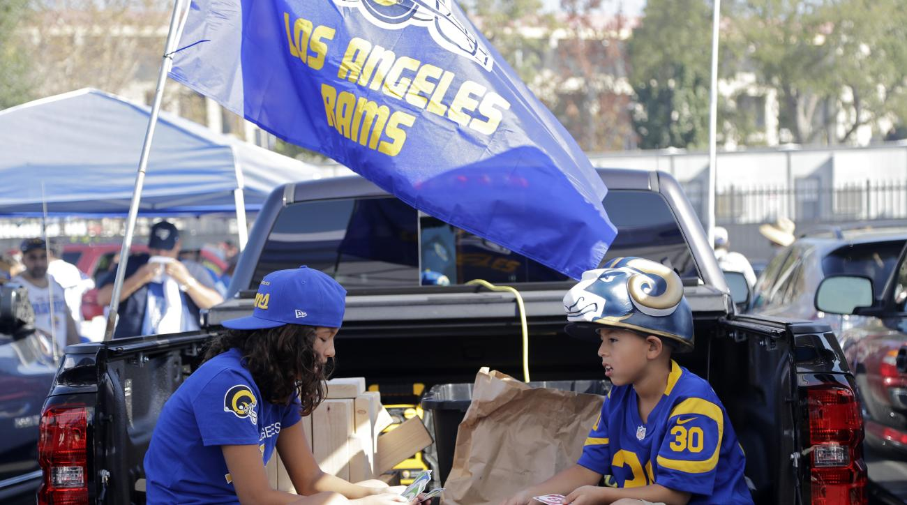 Danielle Robles, left, and Dominic Robles play cards prior to an NFL football game between the Los Angeles Rams and the Seattle Seahawks at the Los Angeles Memorial Coliseum, Sunday, Sept. 18, 2016, in Los Angeles. (AP Photo/Jae Hong)