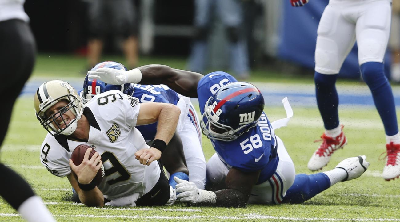 New Orleans Saints quarterback Drew Brees (9) is forced to the ground by New York Giants' Owa Odighizuwa (58) and Jason Pierre-Paul (90) after being tripped up by Leon Hall (25) for a sack during the first half of an NFL football game Sunday, Sept. 18, 20