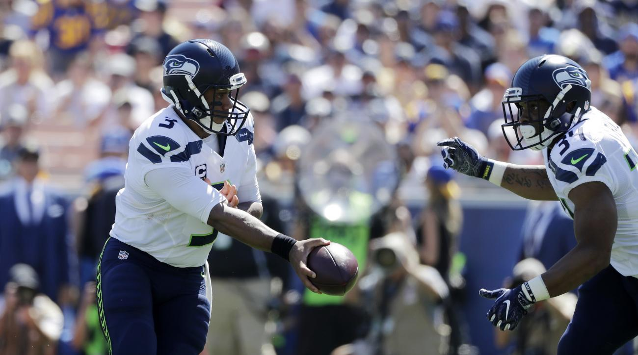 Seattle Seahawks quarterback Russell Wilson, left, hands off to running back Thomas Rawls during the first half an NFL football game at the Los Angeles Memorial Coliseum, Sunday, Sept. 18, 2016, in Los Angeles. (AP Photo/Jae Hong)