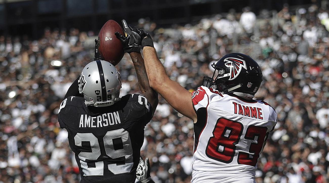 Oakland Raiders cornerback David Amerson (29) intercepts a pass in front of Atlanta Falcons tight end Jacob Tamme (83) during the second half of an NFL football game in Oakland, Calif., Sunday, Sept. 18, 2016. (AP Photo/Marcio Jose Sanchez)