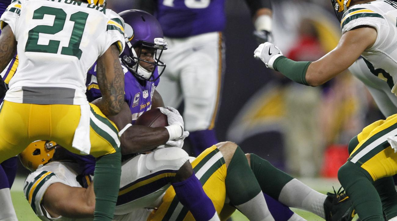 Minnesota Vikings running back Adrian Peterson, center, is tackled by Green Bay Packers outside linebacker Kyler Fackrell, left, during the second half of an NFL football game Sunday, Sept. 18, 2016, in Minneapolis. Peterson was injured on the play and wa