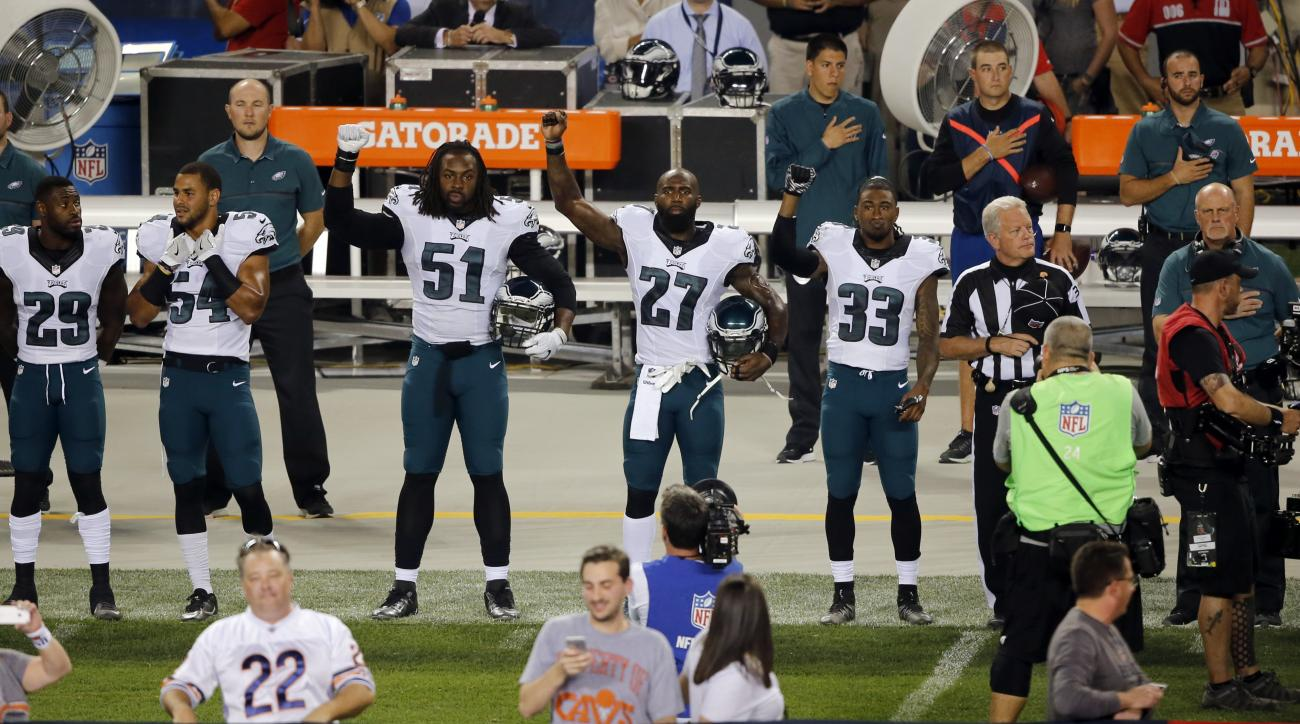 Philadelphia Eagles defensive end Steven Means (51), strong safety Malcolm Jenkins (27) and defensive back Ron Brooks (33) raise their arms during the national anthem before an NFL football game against the Chicago Bears, Monday, Sept. 19, 2016, in Chicag