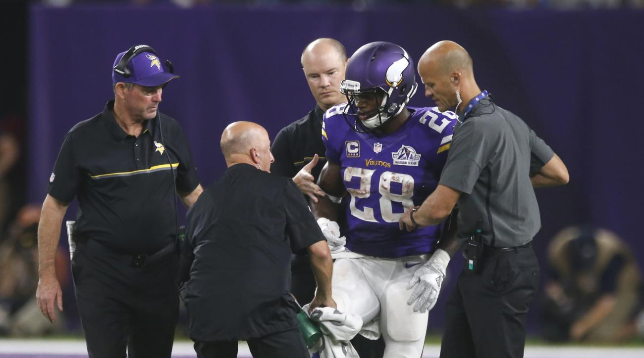 FILE - In this Sept. 18, 2016, file photo, Minnesota Vikings running back Adrian Peterson (28) is helped off the field after getting injured during the second half of an NFL football game against the Green Bay Packers,   in Minneapolis. Peterson will unde
