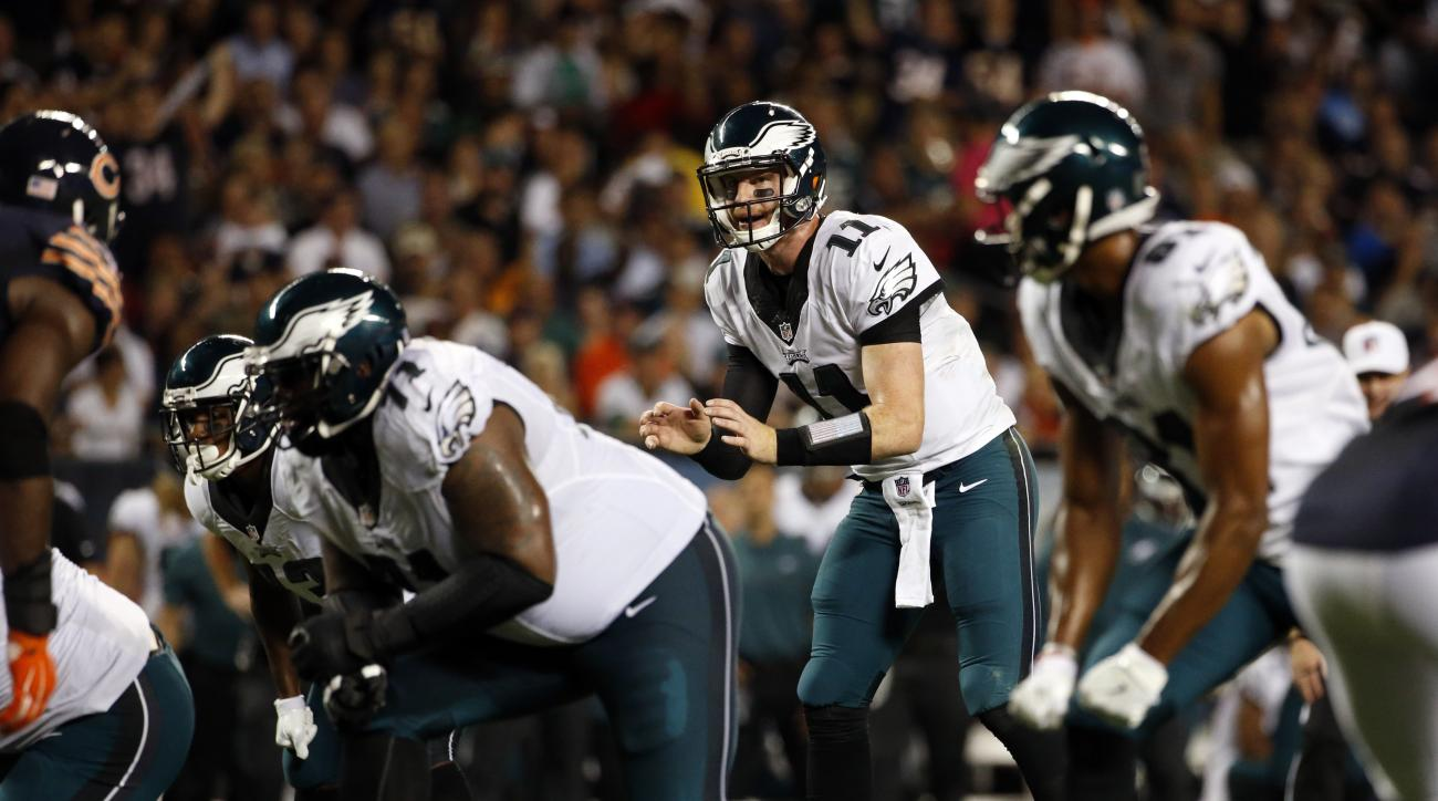 FILE - In this Monday, Sept. 19, 2016, file photo, Philadelphia Eagles quarterback Carson Wentz (11) gets set to take a snap during the first half of an NFL football game against the Chicago Bears in Chicago. After finishing last in the NFL in time of pos