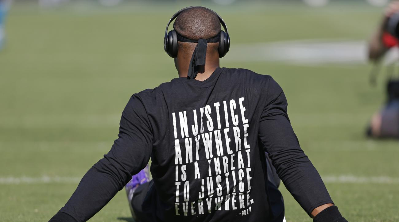 Carolina Panthers' Cam Newton wears a shirt with a quote by Martin Luther King as he warms up before an NFL football game against the Minnesota Vikings in Charlotte, N.C., Sunday, Sept. 25, 2016. (AP Photo/Bob Leverone)