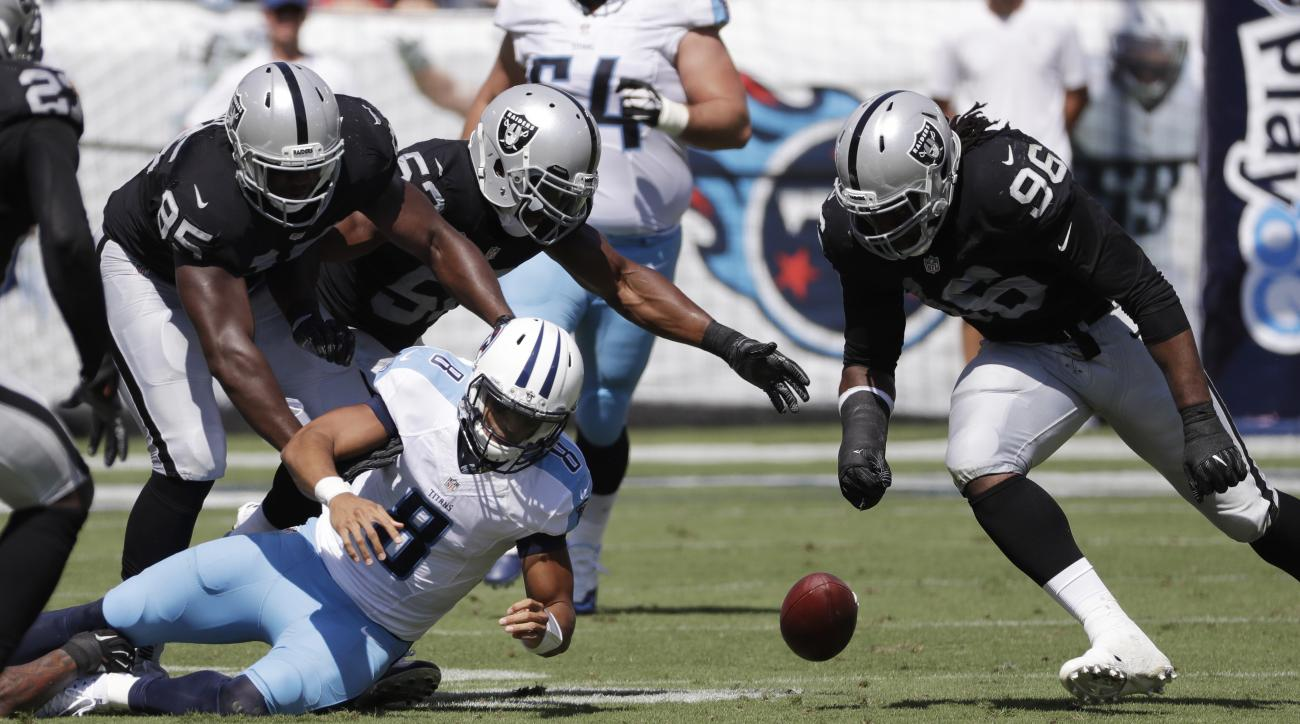Tennessee Titans quarterback Marcus Mariota (8) fumbles the ball as Oakland Raiders defenders Jihad Ward (95) and Denico Autry (96) close in during the first half of an NFL football game Sunday, Sept. 25, 2016, in Nashville, Tenn. The Raiders recovered th