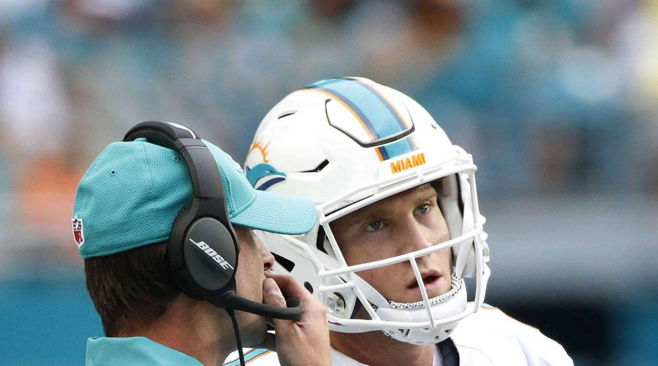 Miami Dolphins head coach Adam Gase speaks with quarterback Ryan Tannehill (17) on the sidelines during the first half of an NFL football game against the Cleveland Browns, Sunday, Sept. 25, 2016, in Miami Gardens, Fla. (AP Photo/Wilfredo Lee)