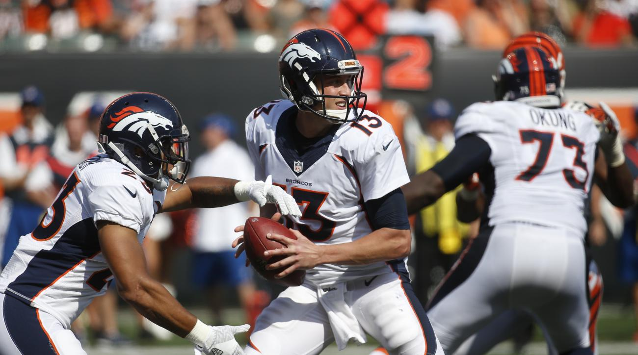 Denver Broncos quarterback Trevor Siemian (13) looks to hand off the ball to running back Devontae Booker (23) during the second half of an NFL football game against the Cincinnati Bengals, Sunday, Sept. 25, 2016, in Cincinnati. (AP Photo/Frank Victores)