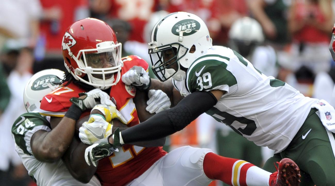 Kansas City Chiefs wide receiver Chris Conley, center, is tackled by New York Jets cornerback Darrelle Revis (24) and running back Bilal Powell (29) during the first half of an NFL football game in Kansas City, Mo., Sunday, Sept. 25, 2016. (AP Photo/Ed Zu