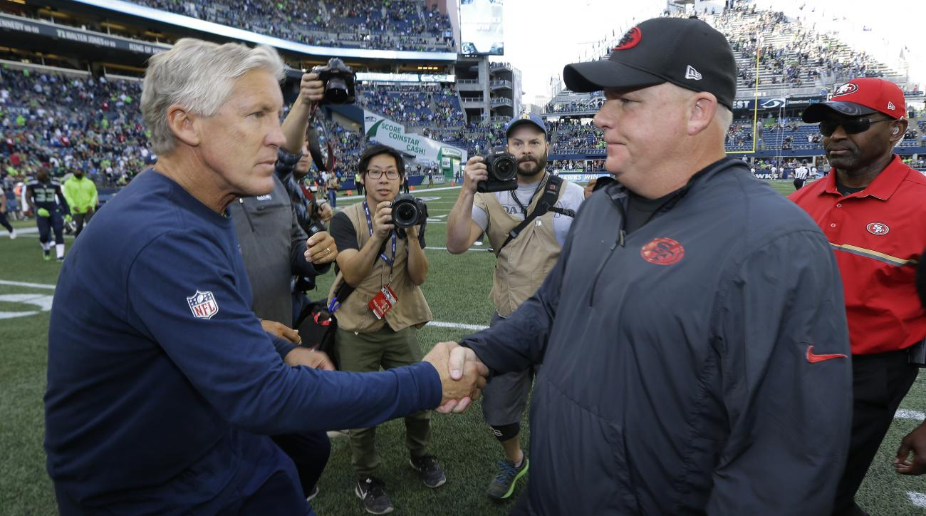 Seattle Seahawks head coach Pete Carroll, left, talks with San Francisco 49ers head coach Chip Kelly, right, following an during an NFL football game, Sunday, Sept. 25, 2016, in Seattle. (AP Photo/Ted S. Warren)