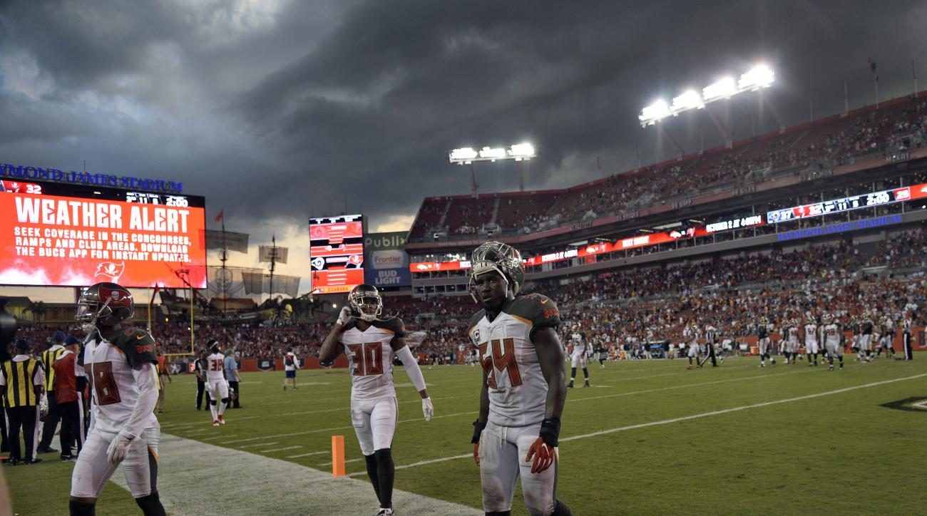 Tampa Bay Buccaneers cornerback Vernon Hargreaves (28), free safety Bradley McDougald (30) and outside linebacker Lavonte David (54) leave the field as storm clouds move over the stadium during the fourth quarter of an NFL football game Sunday, Sept. 25,