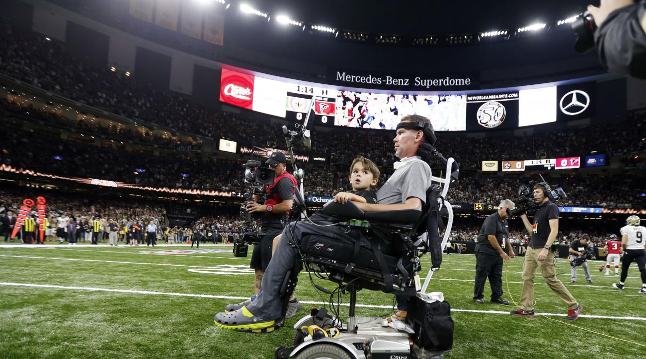 Former New Orleans Saints Steve Gleason rides onto the field for the coin toss with his son before an NFL football game against the Atlanta Falcons in New Orleans, Monday, Sept. 26, 2016. (AP Photo/Gerald Herbert)