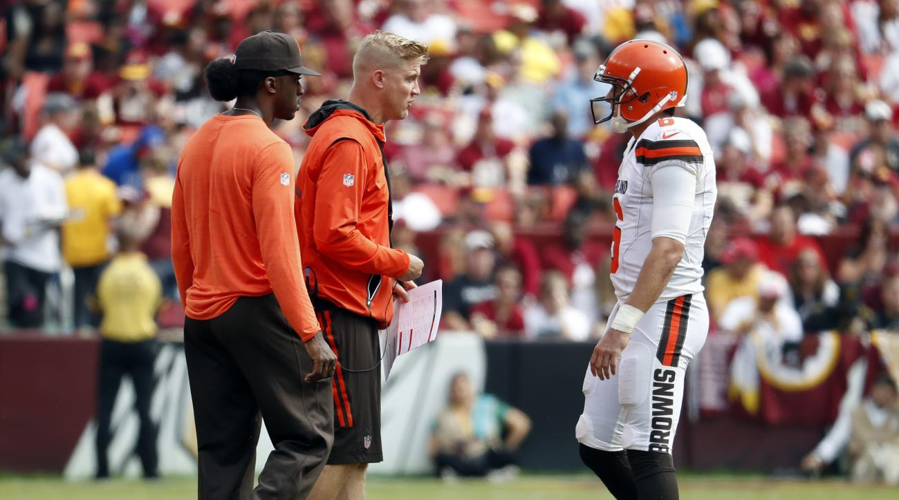 Injured Cleveland Browns quarterbacks Robert Griffin III, left, and Josh McCown talk with quarterback Cody Kessler (6) during the first half of an NFL football game against the Washington Redskins, Sunday, Oct. 2, 2016, in Landover, Md. (AP Photo/Carolyn